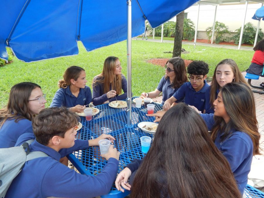 A group of friends enjoy their twenty-five minute lunch break over the new school lunch program, Sage Dining.