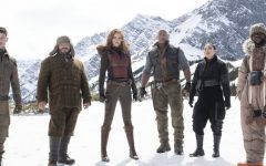(Lest to Right) Nick Jonas, Jack Black, Karen Gillan, Dwayne Johnson, Awkwafina, and Kevin Hart stand in Jumanji's icy tundra before trying to penetrate Jurgan the Brutal's fortress. Unless they can stop him, Jumanji will be a lifeless wasteland forever. (Photo Credit: rogerebert.com)